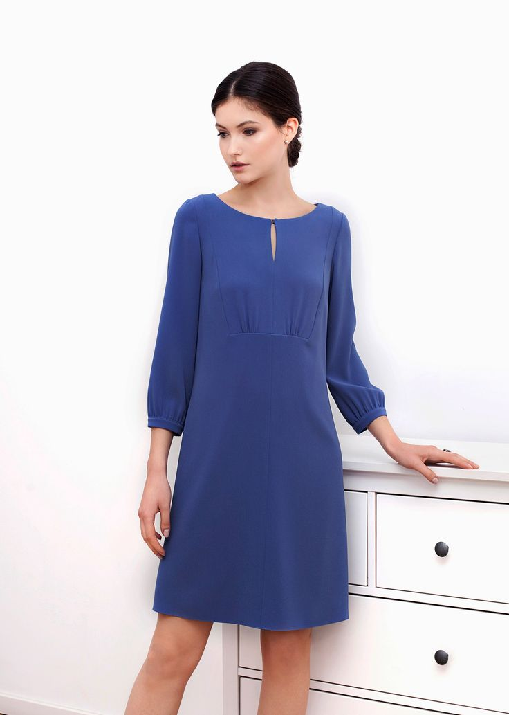 Nicole dress blue. The simple flared line is embellished by gentle folds and beautifully rounded neckline with teardrop fastening. The material displays rich colour and light, fluid texture, defining the effortlessly chic silhouette.