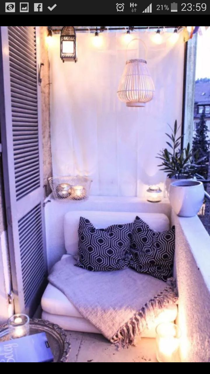 Cozy outdoor patio or nook. Whitewashed with candles and comfortable textiles. Neutral palette.