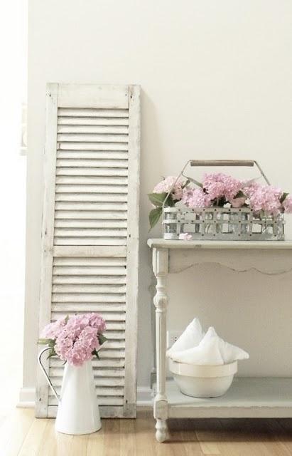 white shutter, pink flowers in bottle holder, on chippy white table