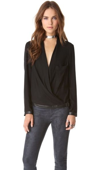Sculptural draping lends soft volume to a single-pocket Helmut Lang blouse. A buckle cinches the leather-trimmed hem, and leather cuffs finish the long sleeves. Semi-sheer.