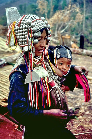 An Akha mother wears a traditional silver headdress as she breastfeeds her young baby and appliques cloth that she will stitch into clothing. At night, she wears her heavy headdress, beads and jewelry to bed. Her babies cap is also decorated with silver coins and glass beads. The Akha, one of the most exquisitely dressed peoples in Asia, are one of several tribes that live in the mountains of China, Thailand, Laos and Burma   © John Spies