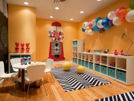 A giant painted gumball machine pops against the vibrant orange walls of this lively playroom. Along with the wall color, the artistic paper lantern fixture, chevron rug, and art table are enough to inspire hours of creative play.