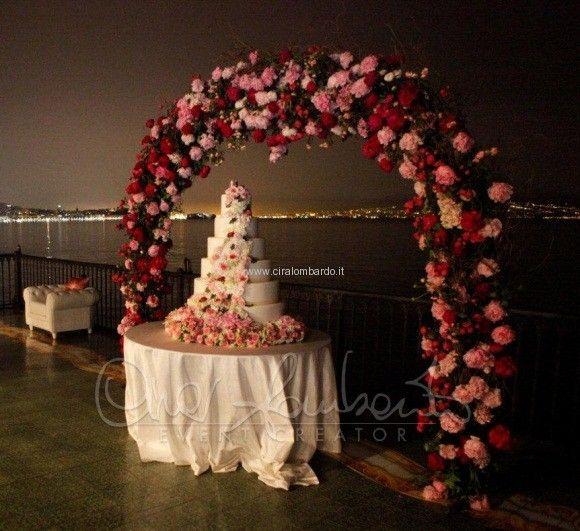 Torta nuziale sotto un arco di fiori. Panorama mozzafiato
