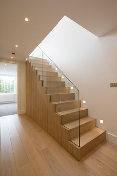 Light and fresh contemporary shell. Pale oak timber floor with neutral wall colour, simple lighting and feature glass balustrade