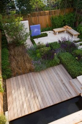 DES:CHARLOTTE ROWE. VIEW ONTO FORMAL TOWN/CITY GARDEN IN LONDON WITH DECKING, POOL, BOX CUBES, SALVIA 'MAINACHT', 'PURPURESCENS' AND 'CARADONNA' AND CAREX BUCHANANII. SEATING AREA