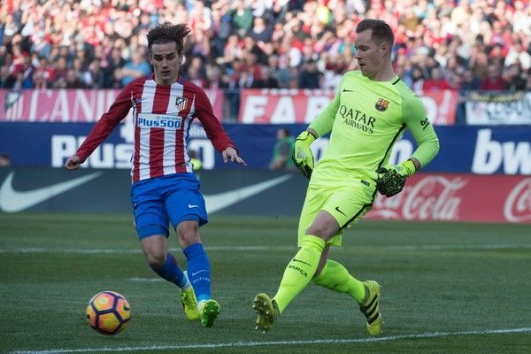 Atletico Madrid's French forward Antoine Griezmann (L) vies with Barcelona's German goalkeeper Marc-Andre Ter Stegen during the Spanish league football match Club Atletico de Madrid vs FC Barcelona at the Vicente Calderon stadium in Madrid on February 26, 2017. / AFP / CURTO DE LA TORRE