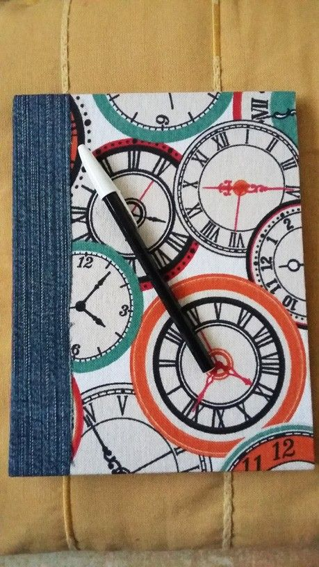 Precioso cuaderno artesanal hecho a mano de 20 x 15 cm con tapas duras forrado en tela de algodón y jean reciclado con diseño de relojes. Costura expuesta en forma de X en color naranja. 3 pliegos de hojas de papel bookcel liso, ideales para dibujar y tomar notas.<br /> Se realizan a pedido. Variedad de telas y estampados.
