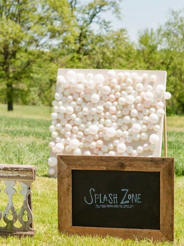 Guests throw darts at balloons filled with paint attached to a canvasOutdoor Wedding Reception Lawn Game Ideas / http://www.deerpearlflowers.com/outdoor-wedding-reception-lawn-game-ideas/2/