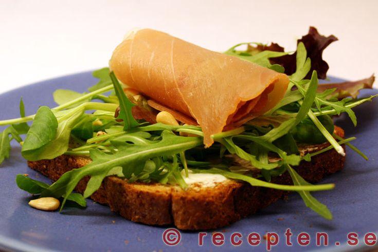 Ett recept på förrätt med en rostad brödskiva med färskost, salladsbädd, limestänk, pinjenötter och lufttorkad skinka. Supergott och superenkelt!