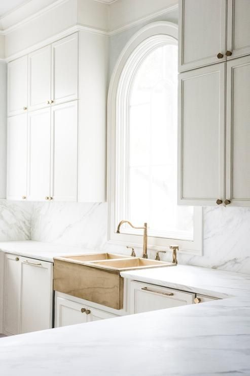 Lovely kitchen features stacked white shaker cabinets adorned with brass hardware paired with white marble countertops and backsplash and a brass apron sink.