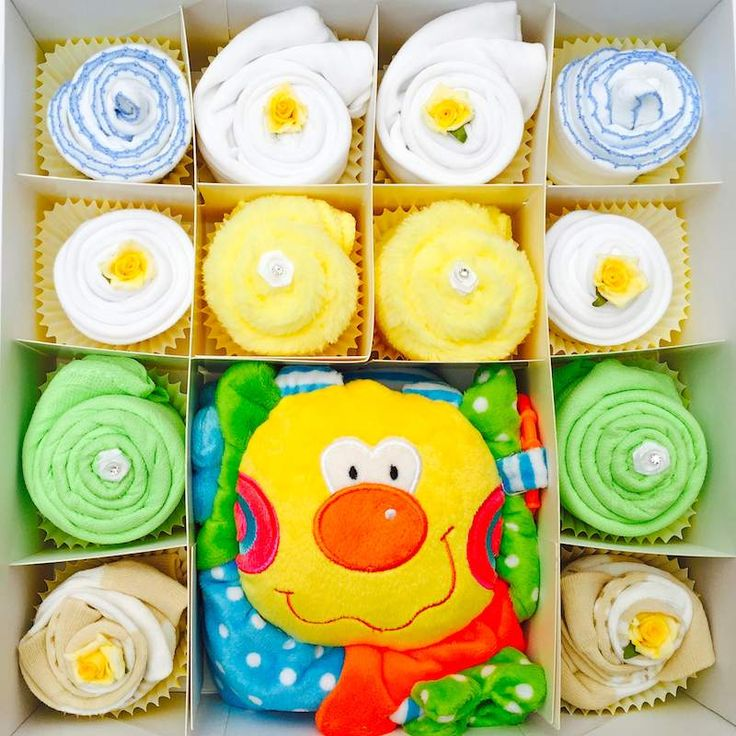 This cupcake gift set will be adored by any little baby boy! Featuring an adorable Flower Rattle. Comes presented in a large white or blue keepsake gift box. Gift wrapped in colour coordinating celephane. Cupcake gift set contents  x1 Large white or blue keepsake gift box x1 Large Plush Flower Rattle (6 months ) x2 white bibs with velcro fastening x2 white and blue bibs x2 White or blue short sleeve bodysuits (0-3 or 3-6 or 6-12) x2 Lime or white cotton muslins x4 pairs of neutral or blue…