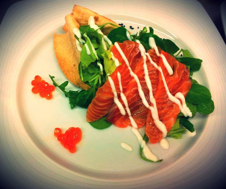 Fresh sheviche salmon with valerian and wild rocket salad in tortilla boat  brik salmon eggs