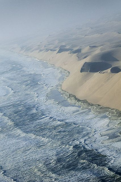 The waves of the Atlantic breaking against the sand cliffs of Namib desert, Namibia.