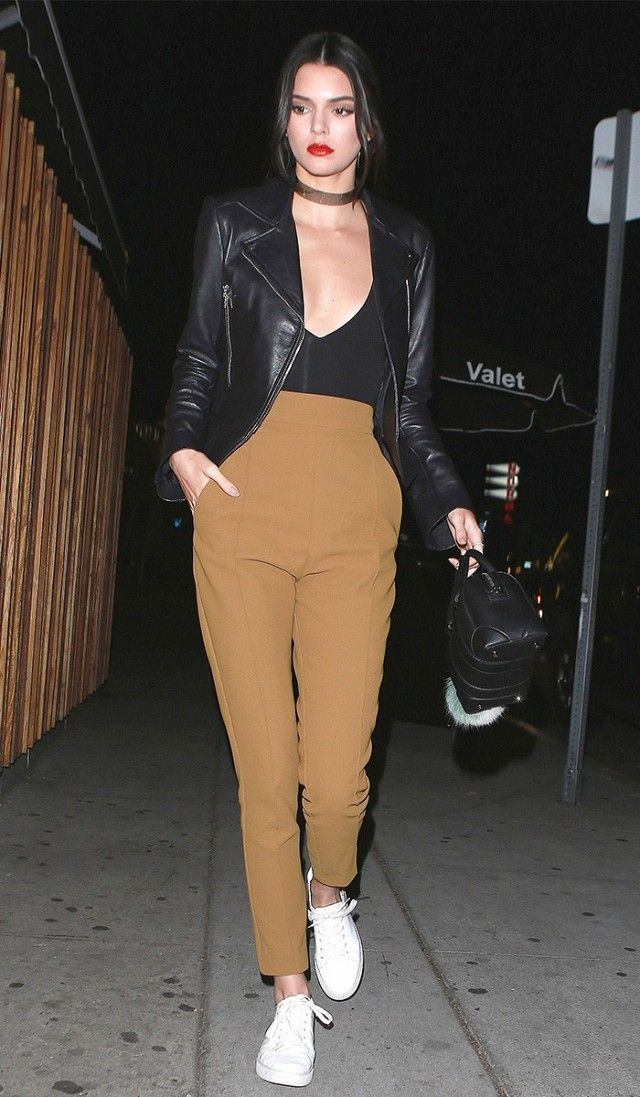 2016: Kendall Jenner wears a black bodysuit, moto jacket, high-waisted trousers, white sneakers, choker, and a mini Givenchy duffle bag