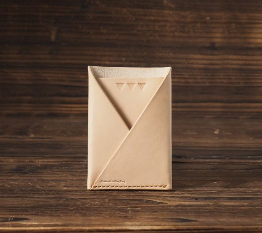 """The Card Wallet is constructed out of two single piece of vegetable tanned leather. Two-pocket card holder. For those that carry multiple cards and some cash. It features one pocket for cash and one slot for cards.  Material: - Vegetable tanned leather (1.6 - 2.0 mm thickness) - Wax thread  Size: - 113 mm (H) x 80 mm (W)  - 4.45 """" (H) x 3.15 """" (W)  Details: - 100% handcrafted, made to order - Color: Natural Nude _____________________________________________________________ ** Please note…"""