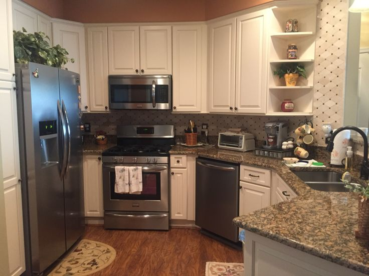 Small, condo kitchen remodel finally complete! Pergo wood flooring, buttermilk cabinets, Giallo Vicenza granite countertops, marble tile backsplash, oil rubbed bronze faucet and cabinet hardware, pendant light plus recessed lights, and Frigidaire Gallery smudge-proof stainless steel appliances.   August 2016