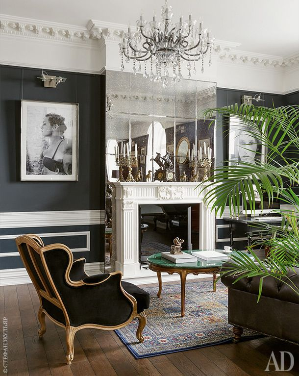 Фрагмент гостиной. Фотографии по бокам от мраморного камина — работа Максима Канищева, хозяина квартиры. На переднем плане кресло, Eichholtz. Сам камин действующий — дымоход здесь был с момента постройки.