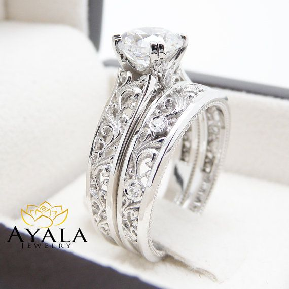 As delicate as a love letter, this unique diamond engagement ring is to be cherished for a lifetime. Handmade in expert detail, 14K white gold mounting glistening diamonds in a perfect balance of design. A unique diamond sits atop in breathtaking detail. This art deco bridal ring set also includes a diamond encrusted wedding band that fits within the design for a seamless look when worn. As an heirloom quality engagement ring set, it will make a worthy accessory to wear every day as a…