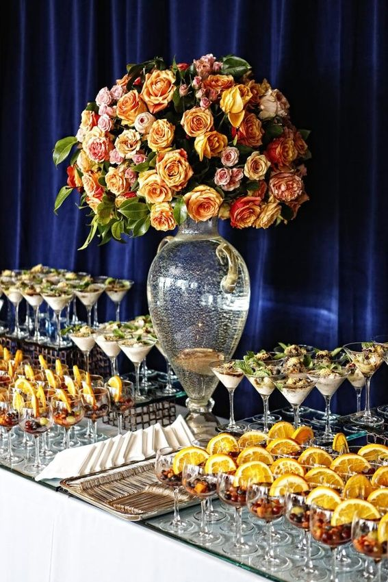 Fresh fruit and a creamy desserts were elegantly served in wine and martini glasses. #FloralArrangement #DessertTable Photography: Tomas Ramos Photographers. Read More: https://www.insideweddings.com/weddings/houston-indian-wedding-celebration-with-800-person-guest-list/435/
