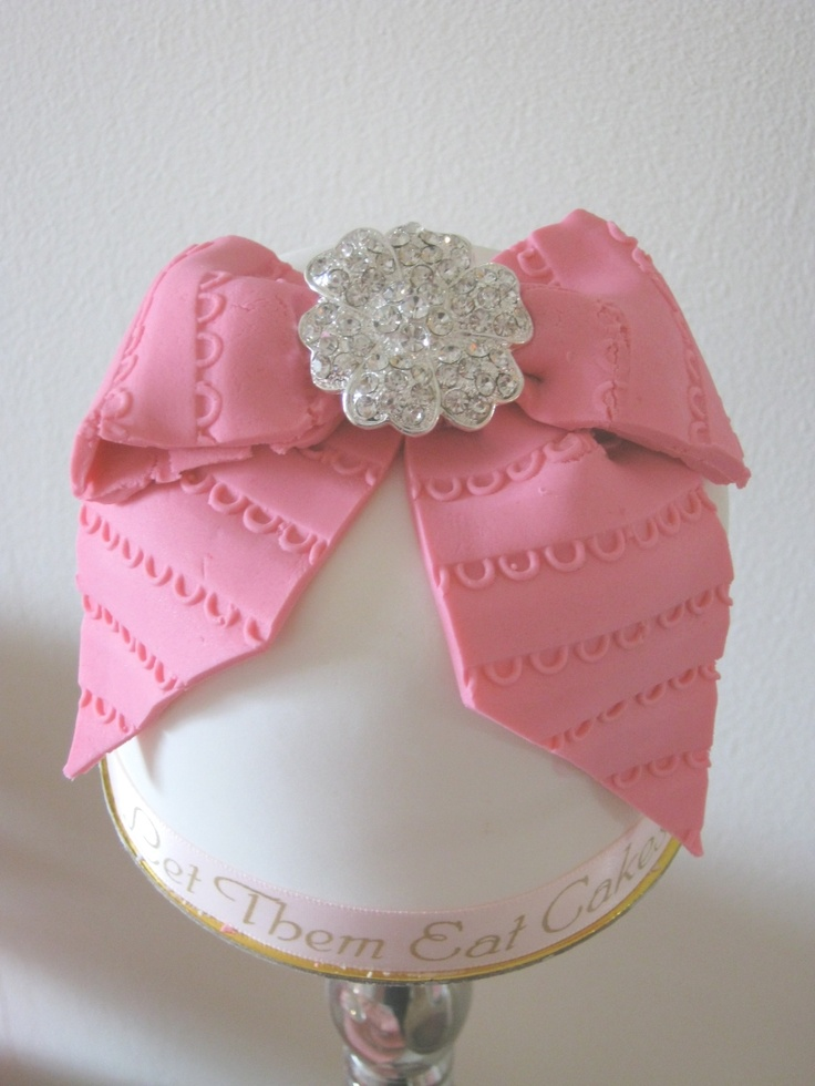 mini cake. Perfect example - beautiful to look at, but by the time  you took off the fondant/gum paste bow and the fondant covering and border, what is left?????