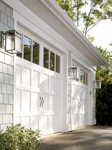 Clopay Reserve Collection wood garage doors painted white rom Midwest Living 2006 Idea Home in Egg Harbor, Wisconsin. Light fixtures echo shape of the door panels and windows.