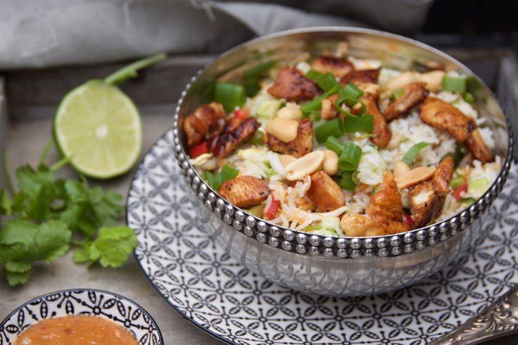 <ul><li><b>1.</b> Marineer 15 minuten de reepjes kip in een mengsel van: Ketjap, geperste knoflook, (1 el) sesamolie. Kook de rijst volgens de verpakking en laat deze afkoelen. </li><li><b>2.</b> Maak de dressing van: limoen, pindakaas, honing, sambal, sesamolie (1 el), sesamzaad, peper en zout naar smaak.</li><li><b>3.</b> Bak de kip gaar. Meng de rijst met gesneden groenten, pinda's, kip, dressing en garneer met lente-ui en koriander.</li></ul>
