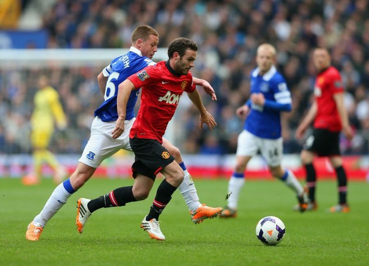 Juan Mata and James McCarthy of Everton battle for the ball.