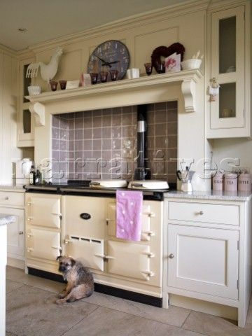 Brown tiled splashback above recessed range oven in Gloucestershire farmhouse  England  UK