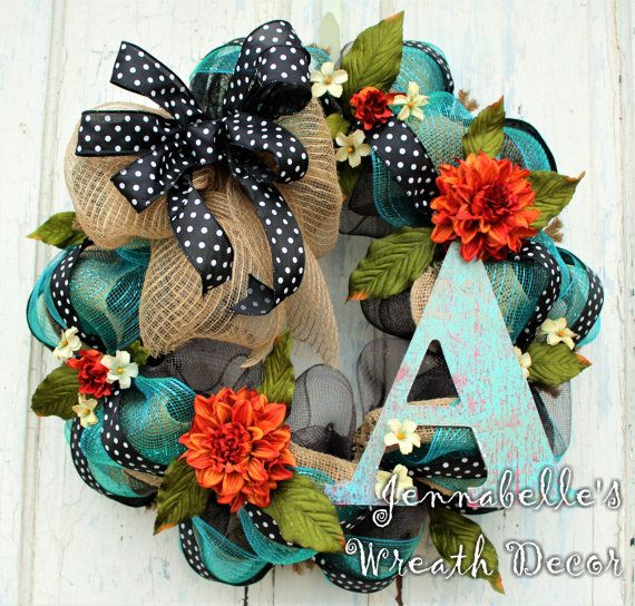 This beauty could stay up on your door from Spring - Fall. This wreath measures approximately 24 inches wide and is 8 inches deep. The base is a solid chocolate brown mesh, wrapped with a natural burlap, and turquoise metallic mesh, and black polka dot wired ribbon. Burnt orange floral and creme accent flowers surround this amazing jute mesh bow mixed with the polka dot wired ribbon. Love! Please indicate which patina inspired 9 inch block letter you will need when purchasing from the…