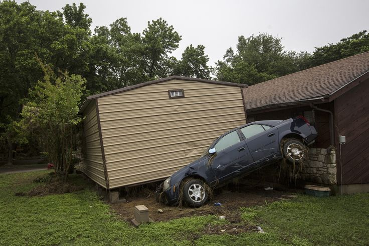 Flood-damaged vehicles and debris are strewn across lawns throughout the length of Bogie Drive in San Marcos, Texas, on May 26, 2015.