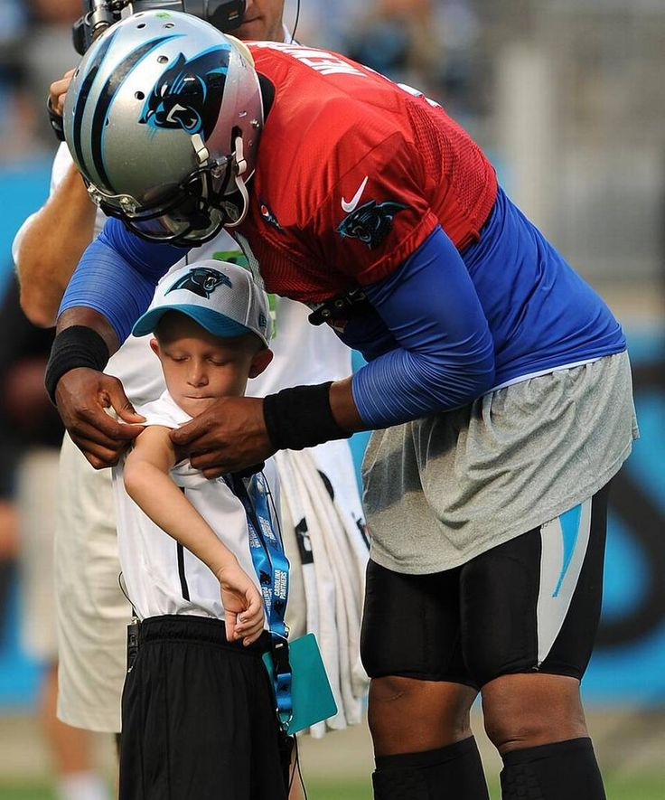 Braylon Beam, 6 yrs., left, has the sleeves of his shirt rolled up by Carolina Panthers quarterback Cam Newton, right, during Fan Fest at Bank of America Stadium on Friday, August 7, 2015. Beam served as Honorary Head Coach through the Make-A-Wish Foundation.