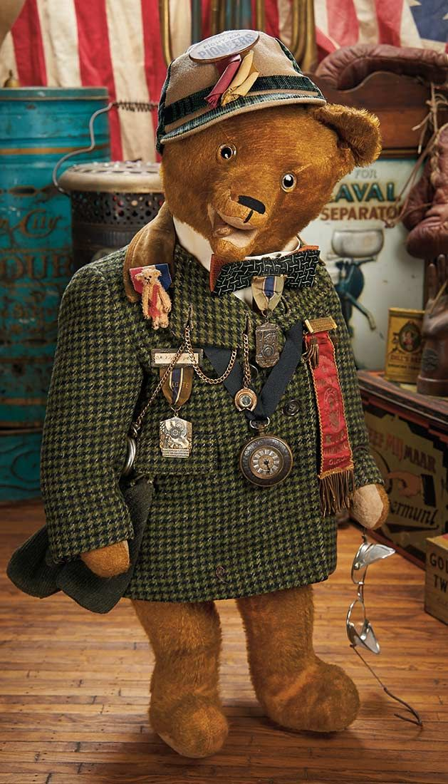 "Vintage Costumed ""Automobile Bear"" circa 1935. Value Points: rare mouth modeling of the friendly bear,wearing antique woolen checkered jacket,white collar and bow tie,and laden with accessories including two fine antique pocket watches,fob,medals and silk badges,with matching cap,mittens,and automobile goggles."