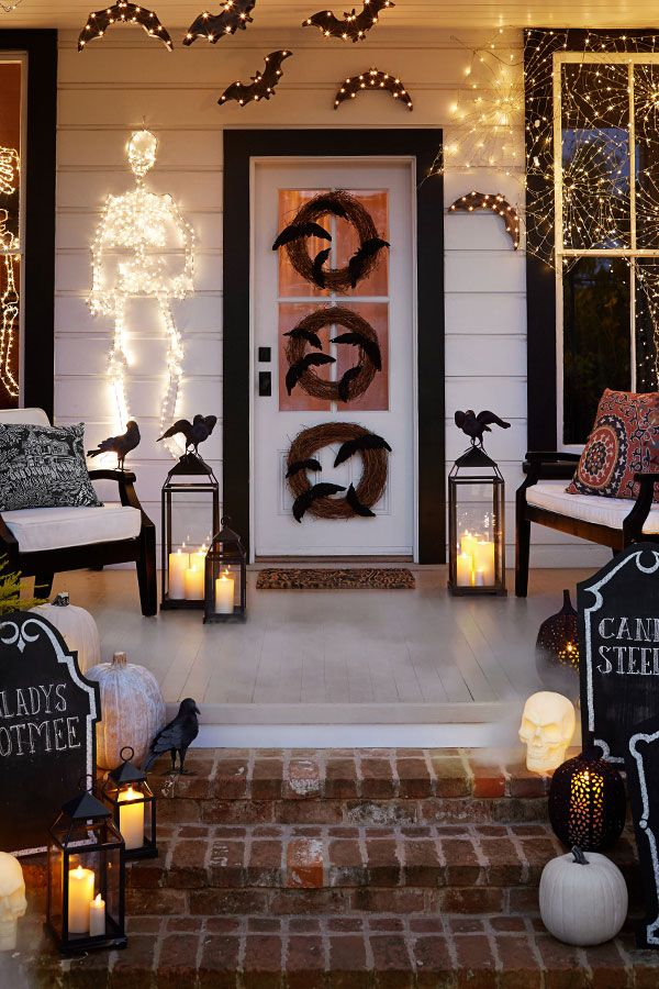A spooky Halloween door couldn't be easier! Place a fun wreath on your front door, layer in lanterns festooned with creepy crows, a few pumpkins (real or faux) and last, add lighting like our spooky skeletons for a style you can easily swap out after the most wicked of holidays!
