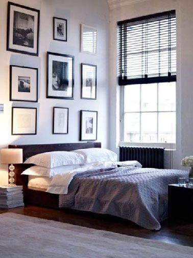 Une chambre parentale blanche et noir qui orchestre sa décoration en fixant un point fort sur l'espace du lit. Contrastant avec les murs blancs,  le noir s'impose pour la tête de lit surmontée du composition de cadres photos eux aussi noirs.