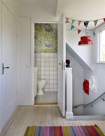 Den gedigna trappan i materialet terrazzo är en snygg detalj och minner om de forna tiderna då huset var tvåfamiljshus. Uppe i hallen finns en liten toalett som är tapetserad med en tapet från Svenskt tenn.