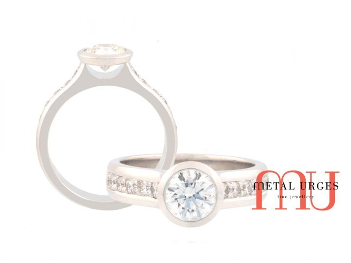 Round cut white diamond and platinum engagement ring.  A GIA certified brilliant cut diamond is centrally bezel set.  The platinum band features grain set white diamond shoulders.  Completely hand made by the Metal Urges team, Tasmania.