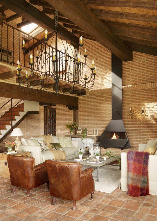 Construcción de salón con dos pisos abiertos, suelo de barro, techo con vigas de madera, puertas de anticuarios y chimenea de diseño.