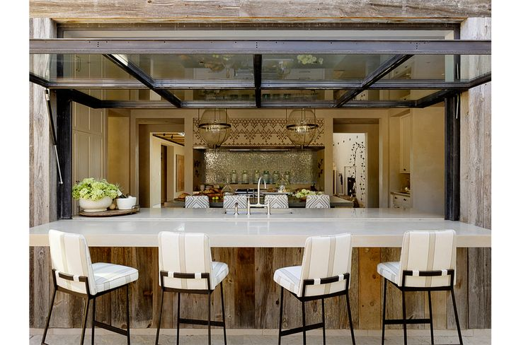 "But the outdoor bar, with its metal and glass garage-style door, surely cuts down on the number of wet feet padding through the kitchen. ""This feature gives the home a resort feel,"" says Lindsteadt. ""This is a place to have fun. You throw up the door and start serving the guests."" By Ken Linsteadt Architects."