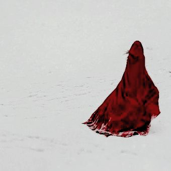 Red riding hood in her red, hooded ccloak running the snow. / Winter