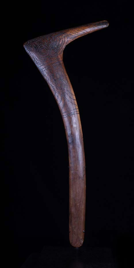"Origin:  Australia, Central Desert, possibly Northern territory        Period/Date: Likely first quarter of the 20th century    Materials:  Mulga wood    Description:  This stunning ""hooked"" or ""number 7"" boomerang is presented on a custom wood display stand.  It is decorated on both sides of the head and neck with pokerwork dotting in meandering totemic patterns."