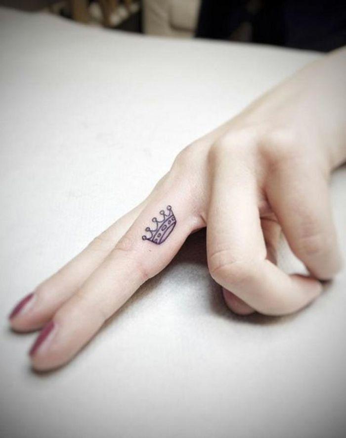 tatuajes en la muñeca, tatuaje minimalista femenino en la parte lateral del dedo medio, pequeña corona
