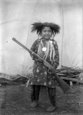 Pierre Paul, a Native American boy on the Flathead Indian Reservation in western Montana, poses while holding an 1894 Winchester rifle in front of a teepee on the reservation. He wears a fur roach on his head and several beaded necklaces around his neck.