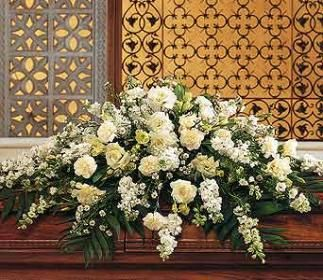 Funeral casket spray with all white flowers.