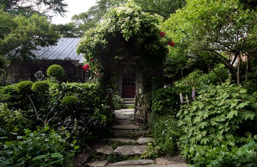 """When landscape designer David Ellis bought this Virginia-Highland home in 1997, the front yard was filled with dead shrubs, poison ivy and crab grass. """"There was nothing worth saving,"""" said Ellis, of Ellis LanDesign. He added the rustic fence and uses topiary-like holly trees, foxgloves and flowering vines such as clematis and roses for a decidedly English touch."""