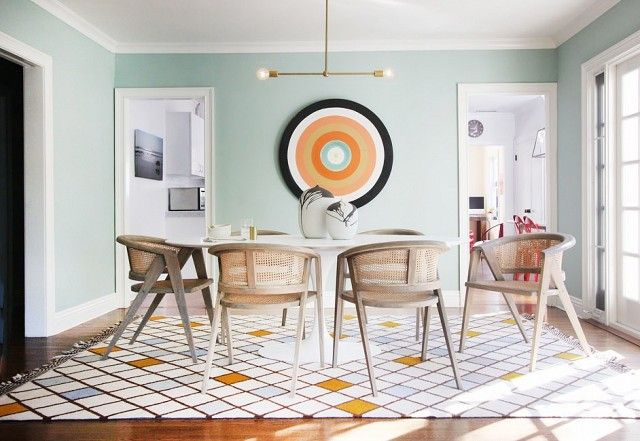 Colorful dining room with sea foam green walls, a large bullseye art piece, a chandelier, and matching dining room chairs