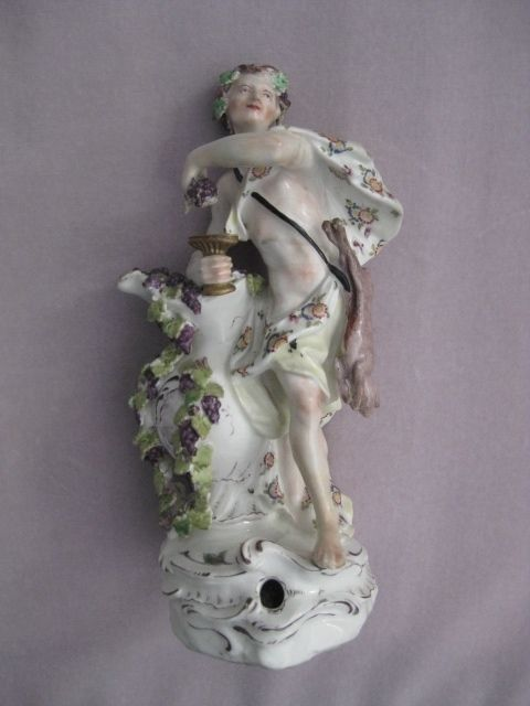 A rare Bow figure of  Autumn depicted as Bacchus standing on a fenestrated rococco base. He holds grapes and a goblet and has a hare hanging at his side. Unmarked  Circa 1758  Height 10""