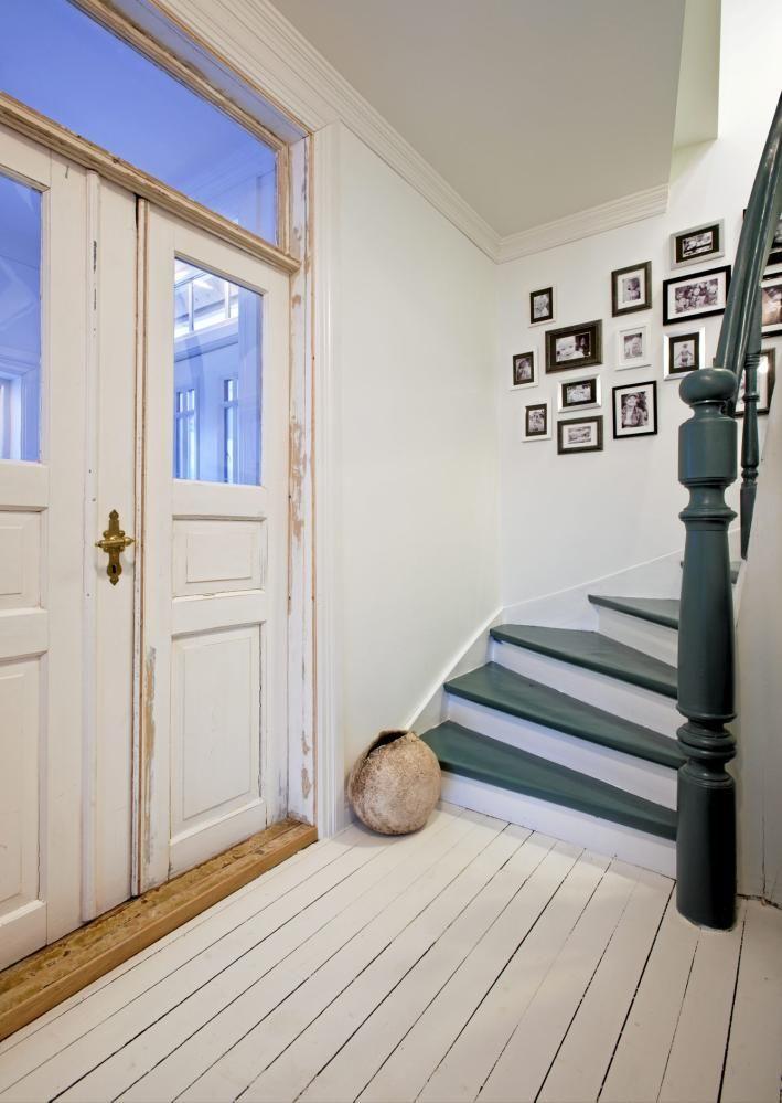 Trappetrinn og gelender har blitt malt i en dyp grønn farge som gir trappen autoritet. Den hvite veggen er dekorert av innrammede svart-hvitt bilder. Gulvet er hvitmalt tre, og inngangsdøren har et rustikk preg.
