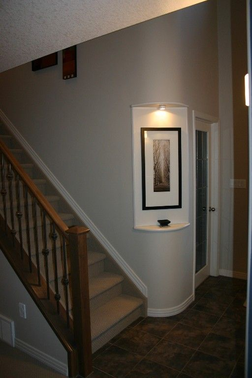 Beautiful way to display an art piece - round corner niche with light.