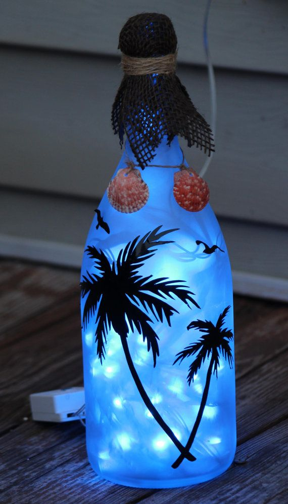 Beautiful wine bottle decorated with vinyl palm trees and birds, while seashells hang from the top. The bottle is filled with LED lights