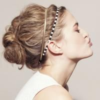 Flair -  Toupeer je haar aan de kruin. Maak een middelhoge nonchalante knot. Breng twee verschillende bandjes aan die je een tweetal centimeter uit elkaar zet. Met een puntkam trek je wat volume in het haar tussen de haarbandjes.